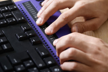 A pair of hands touches a braille display.