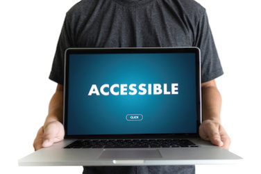 "A man holds an open laptop.  On the screen the word ""Accessible."""