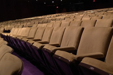 Dimly lighted, several rows of beige chairs in a theater.
