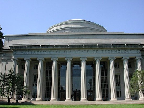 "Facade of gray building with a colonnade of 10 round 30 feet tall columns. Along the facade, over the columns, carved is the phrase ""Massachusetts Institute of Technology"". A dome sits atop the building."