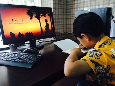 A boy writes on  notebook in front of  screen